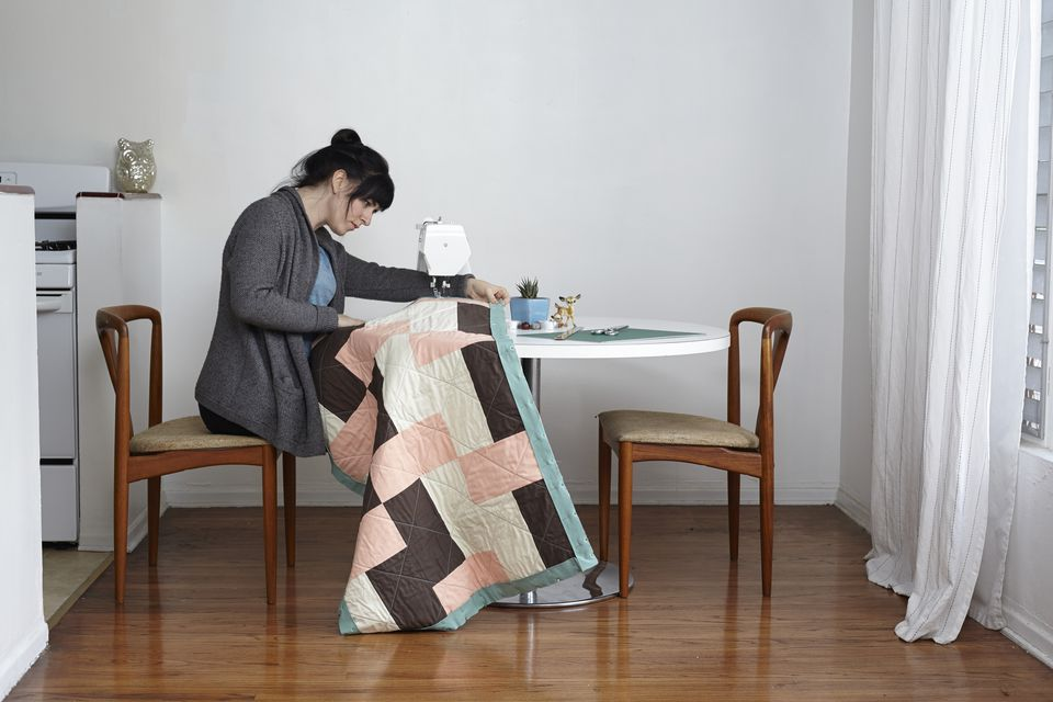 Woman making quilt on sewing machine at home