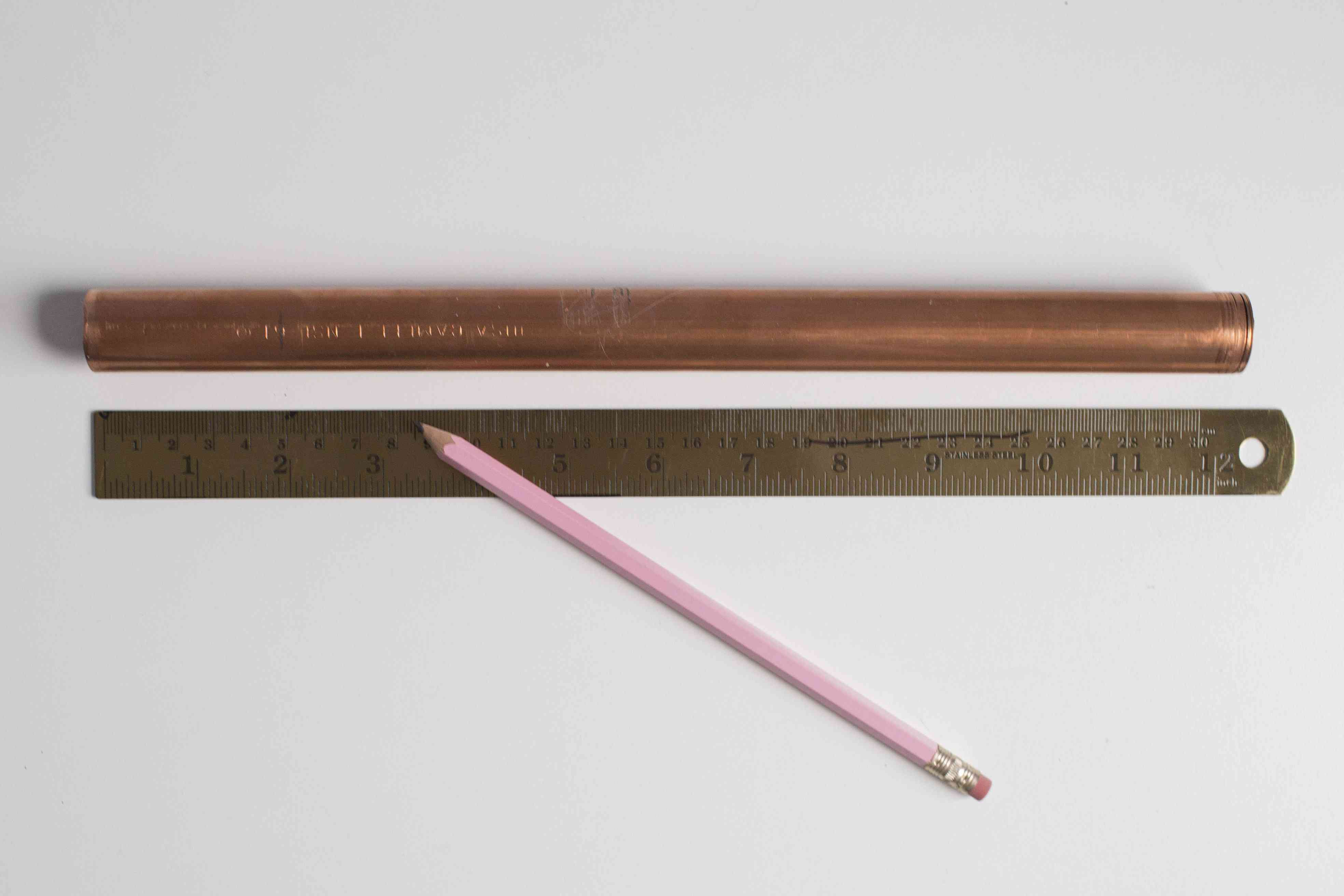 A pencil and ruler next to a piece of copper pipe