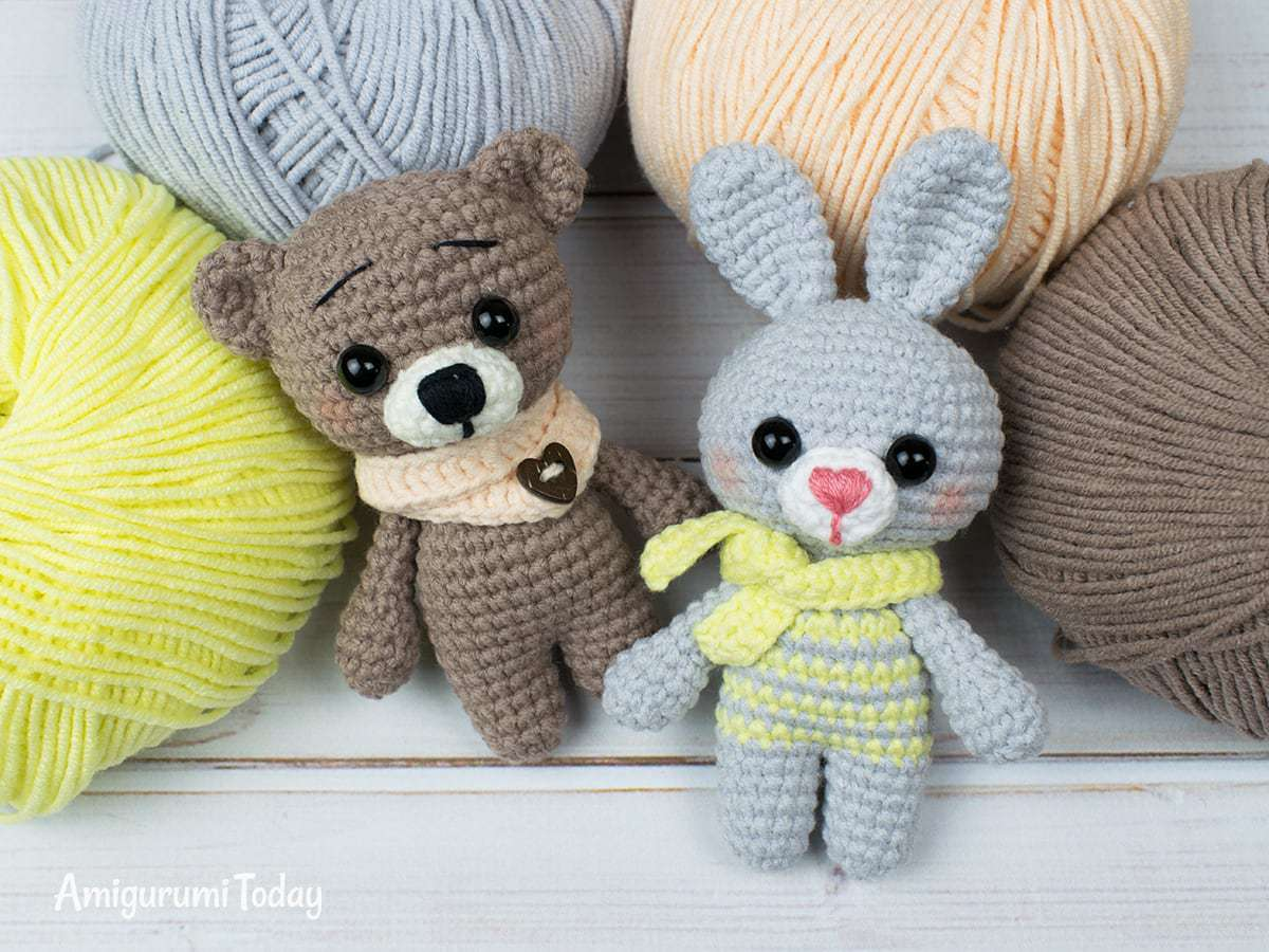 A crochet bunny and bear laying near balls of yarn.