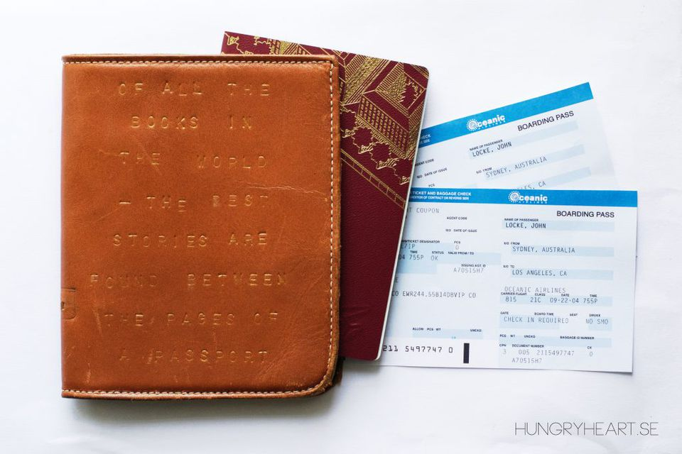 A leather passport holder and plane tickets