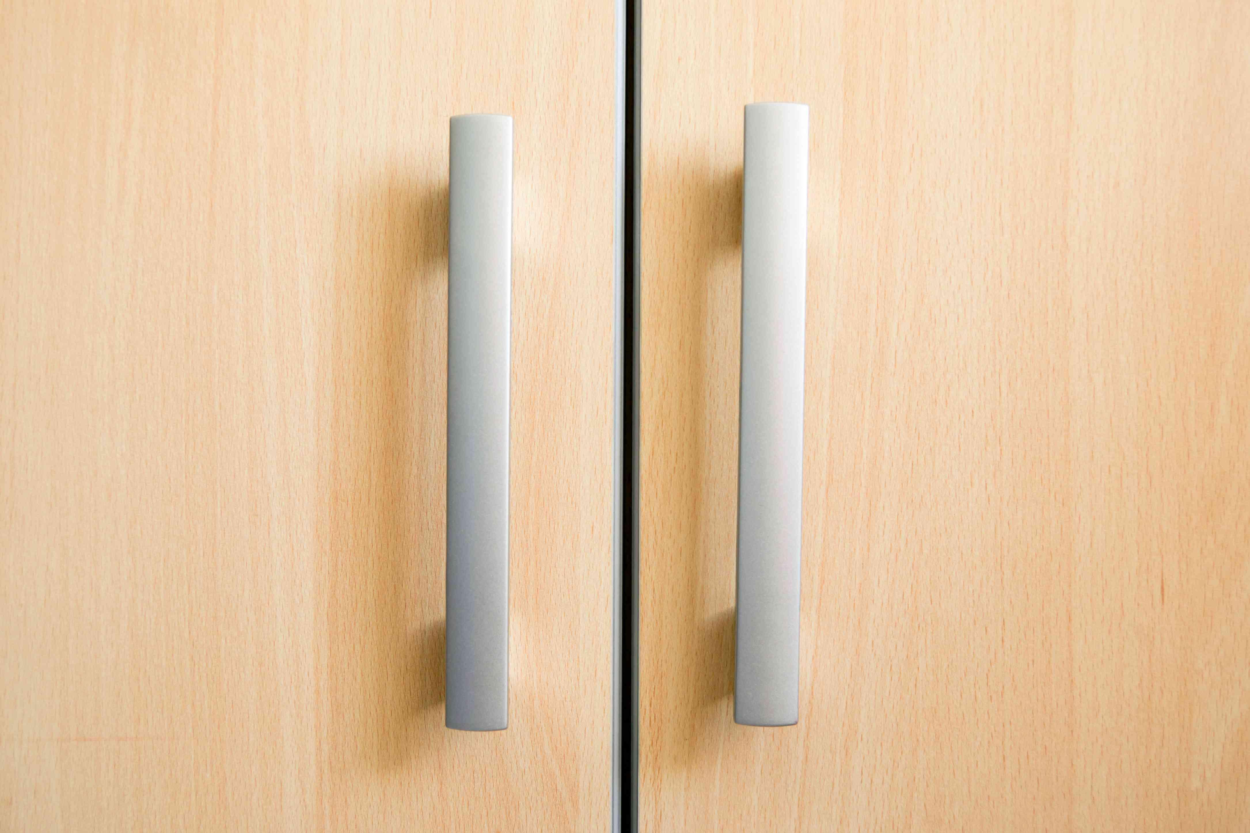 The handles of a slab cabinet door