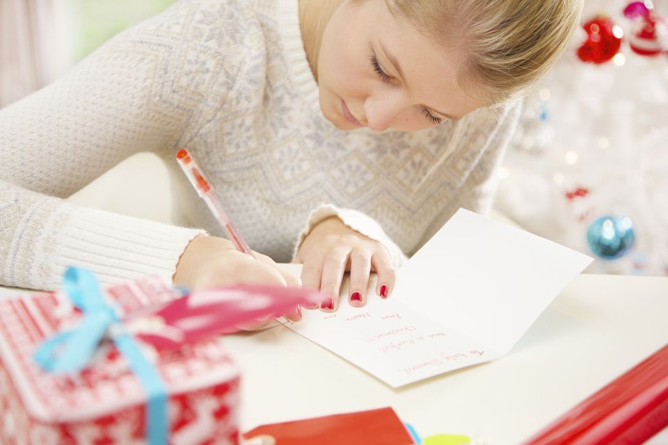 A woman writing a Christmas thank you note