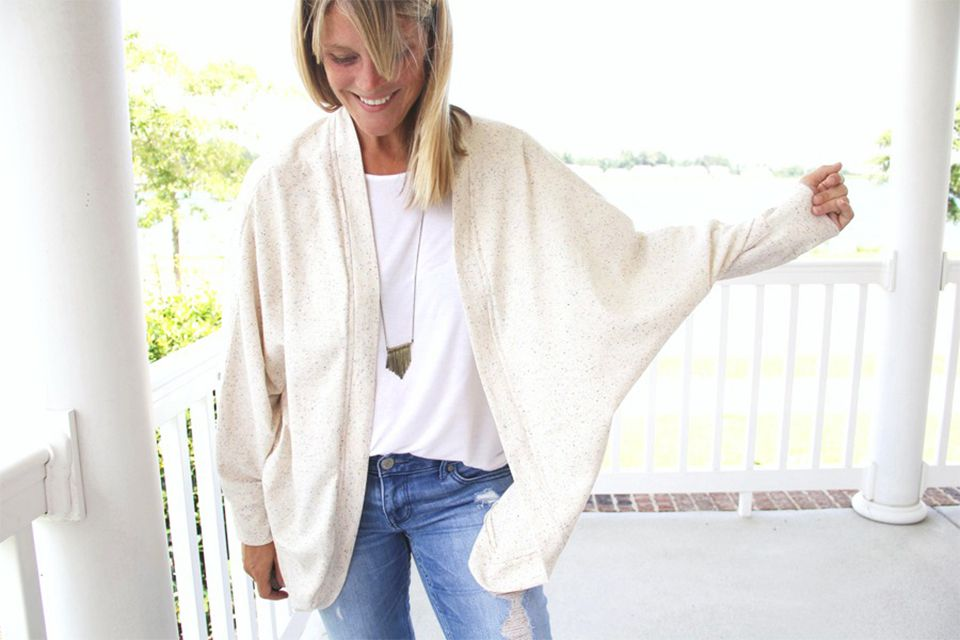 A woman on a porch wearing a white cardigan