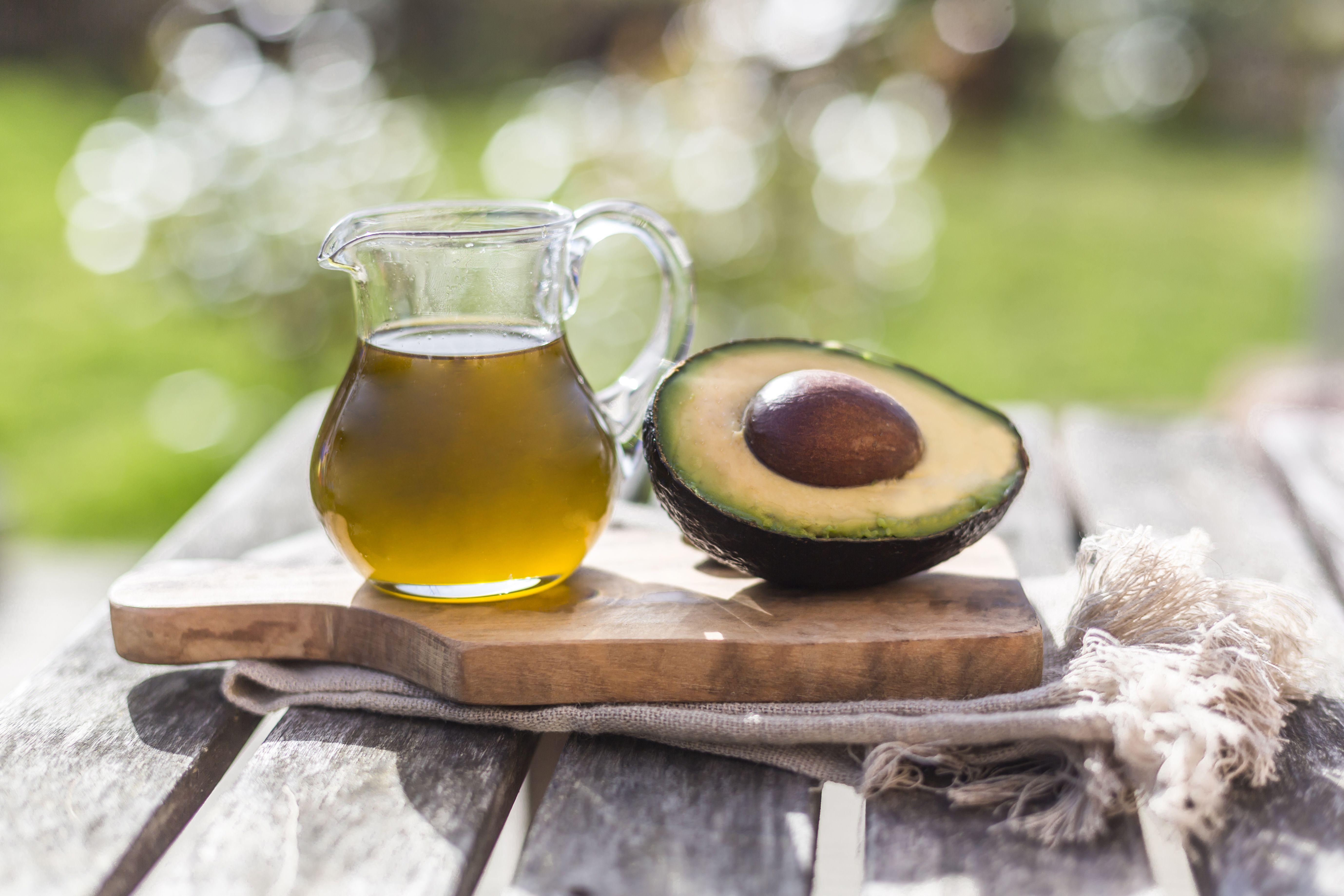 Half of avocado and glass jug of avocado oil on wooden board
