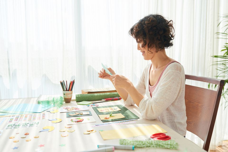 Woman scrapbooking at kitchen table