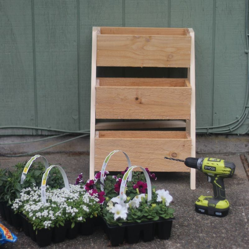 A cedar planter with a drill and flowers