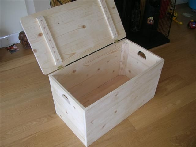 An empty wooden storage box with handles and a lid