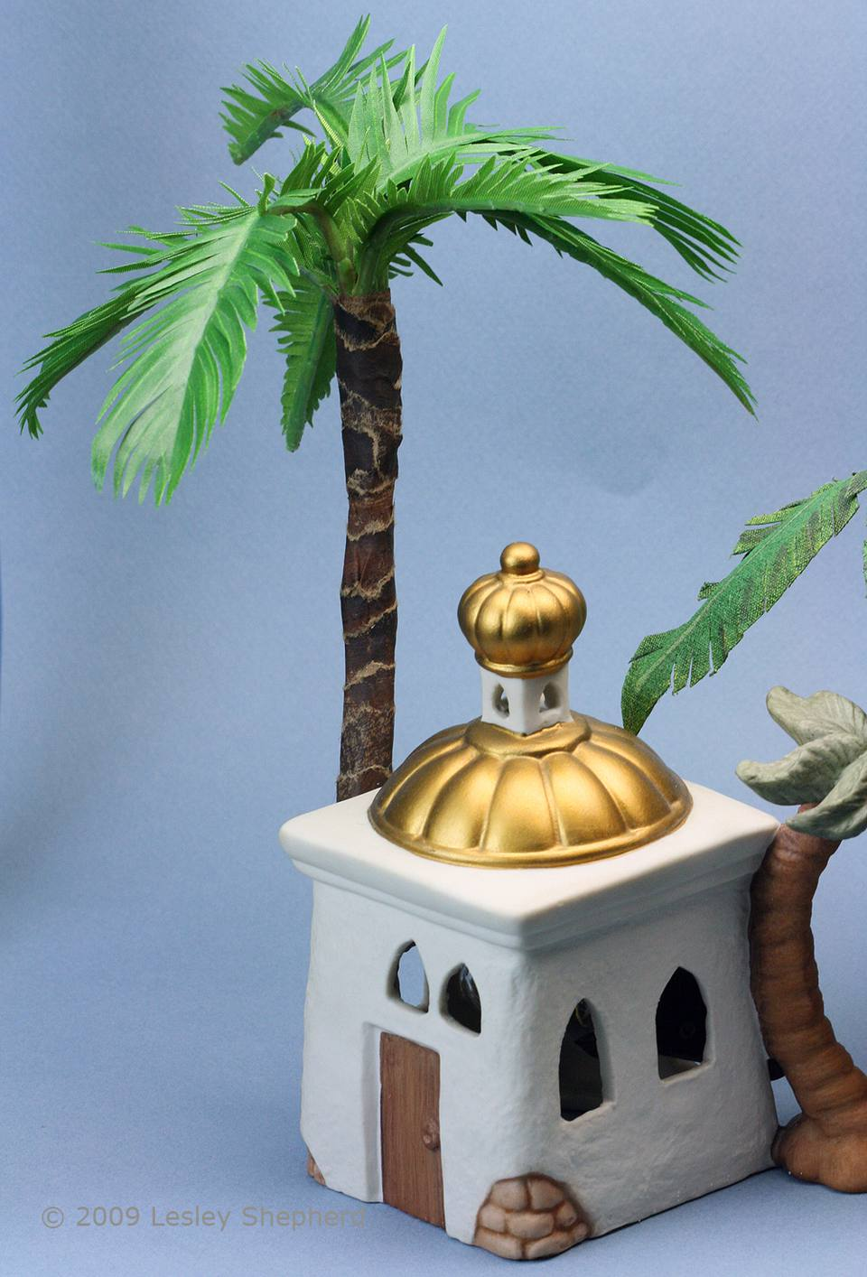 Scale miniature palm tree set behind a porcelain building in a Christmas Nativity set.