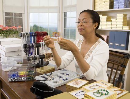 Mature woman making beaded jewelry in home office