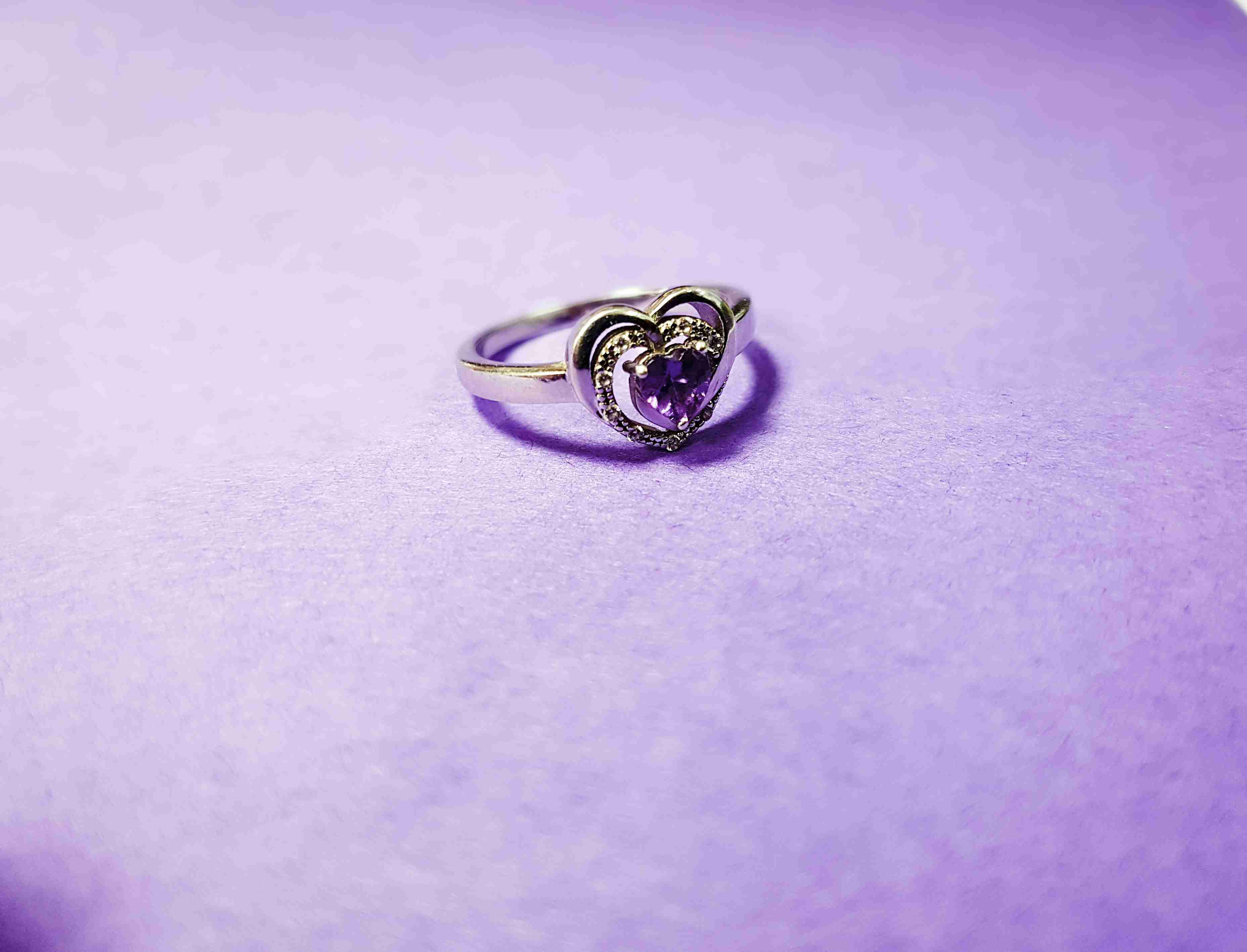 Heart-shaped ring against purple background