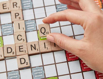 person playing a q in scrabble