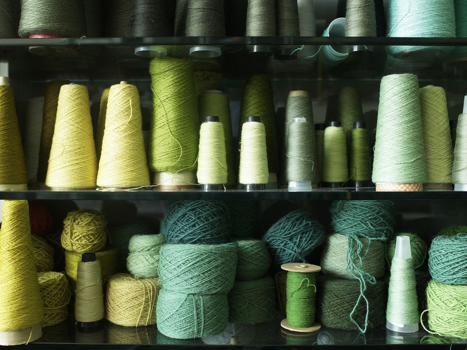 Spools of thread in a range of colors and sizes arranged on three shelves.