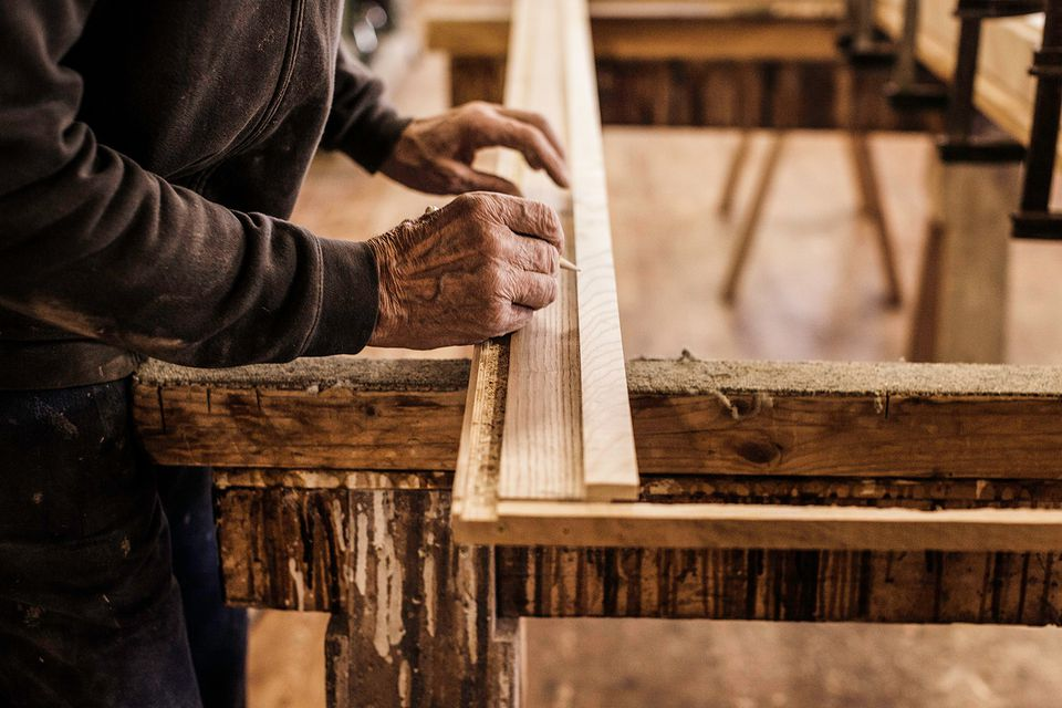 Carpenter's hands measuring wood frame.