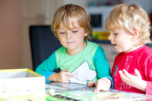Two blond boys playing a board game at home.