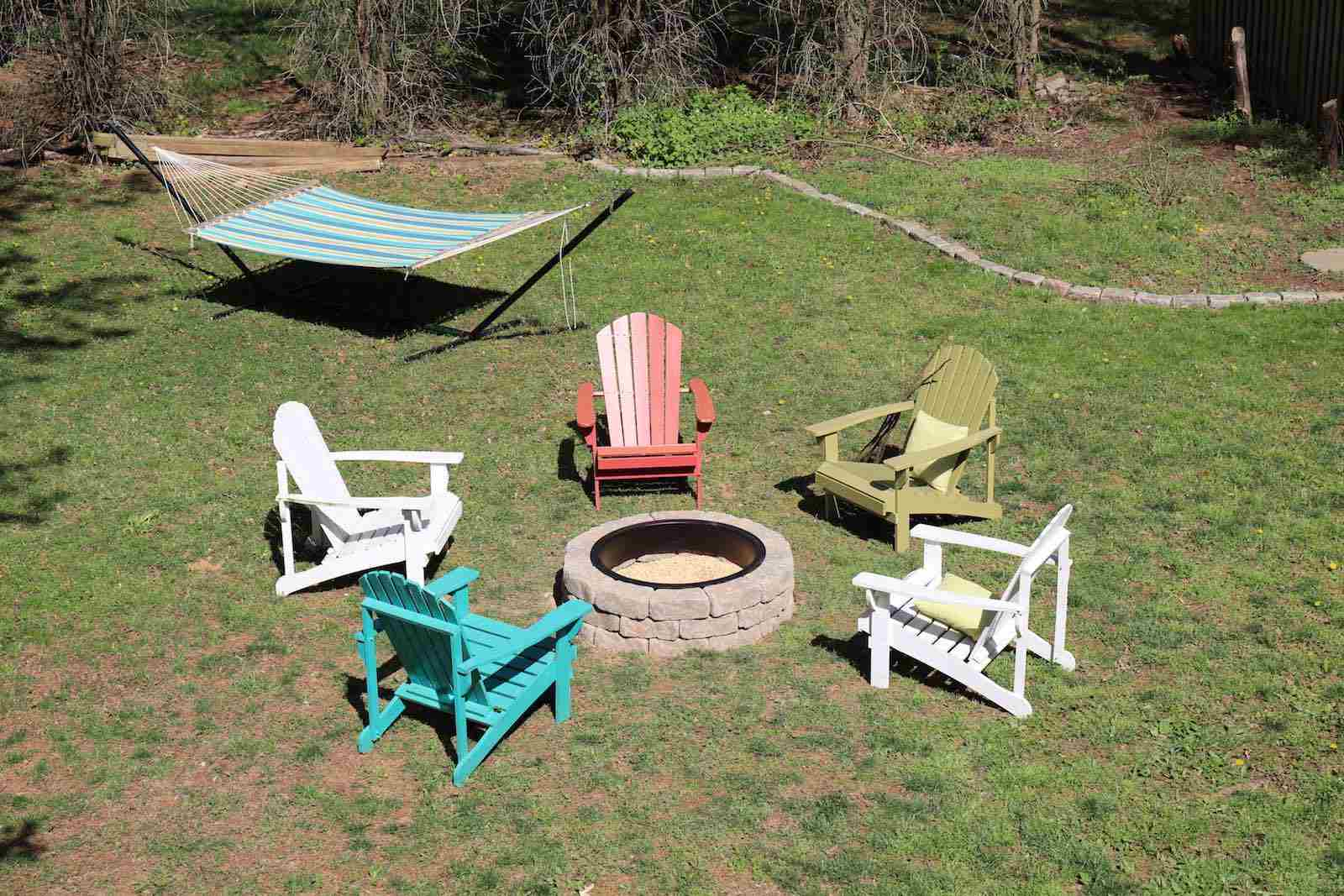 A large backyard with a fire pit, chairs, and hammock
