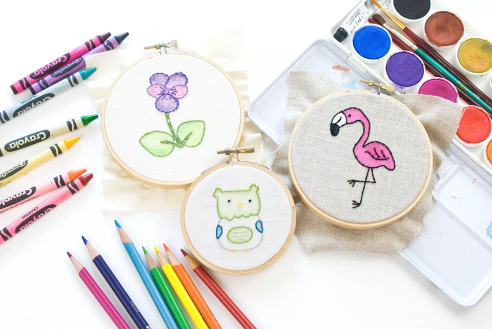 Three embroidery pieces in hoops surrounded by watercolor, crayons, and colored pencils