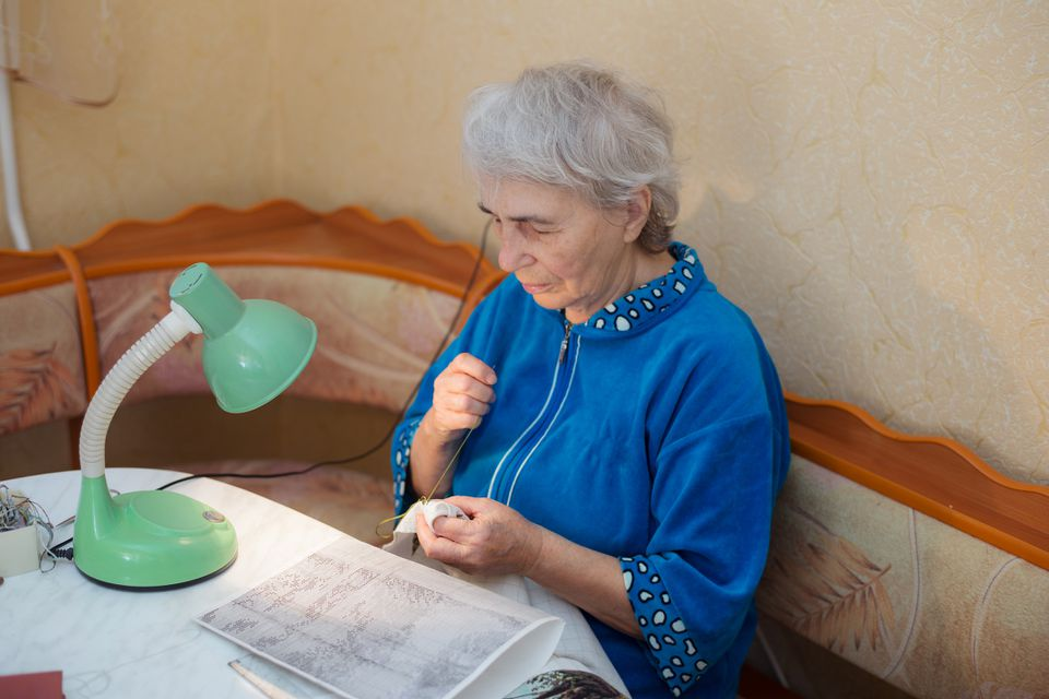 Woman using lamp while stitching