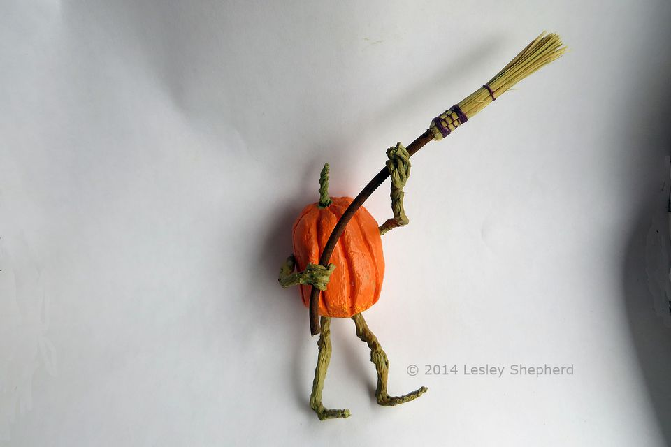 Traditional cobweb broom in miniature, wielded by a miniature pumpkin character.