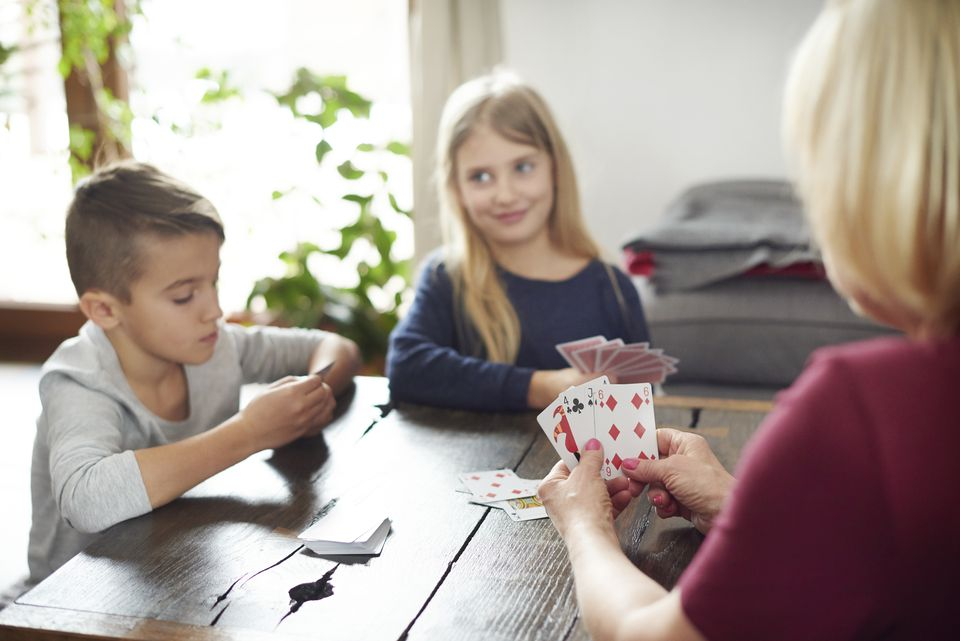Grandmother and grandchildren playing cards at home