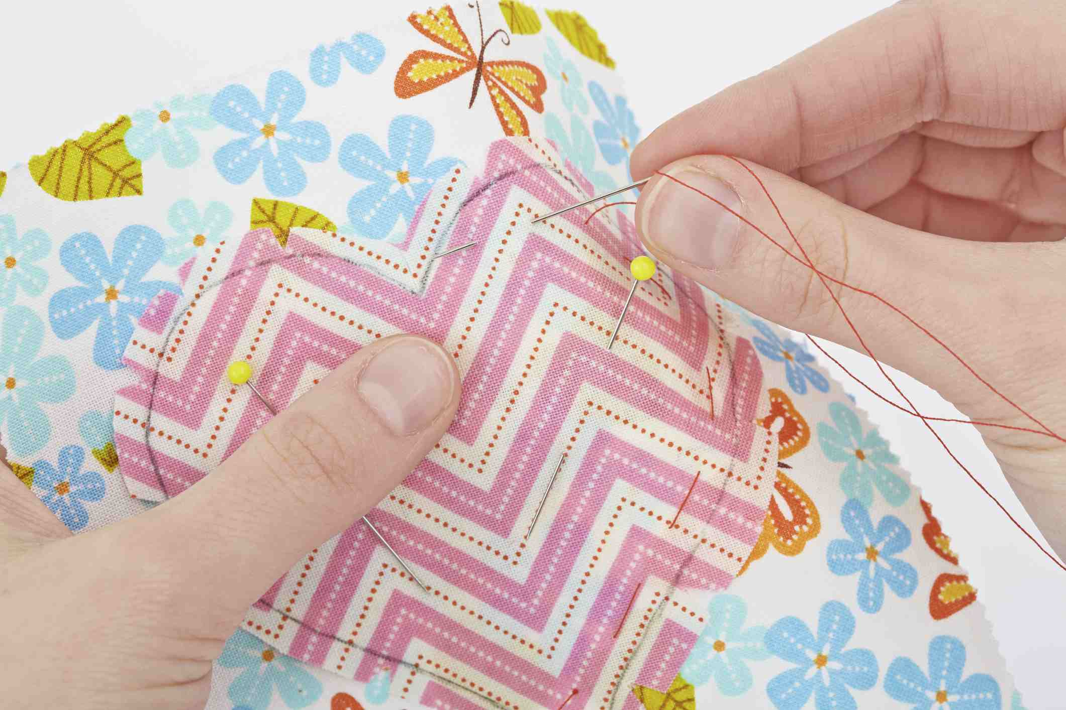 woman sewing quilt patch with sharps needle