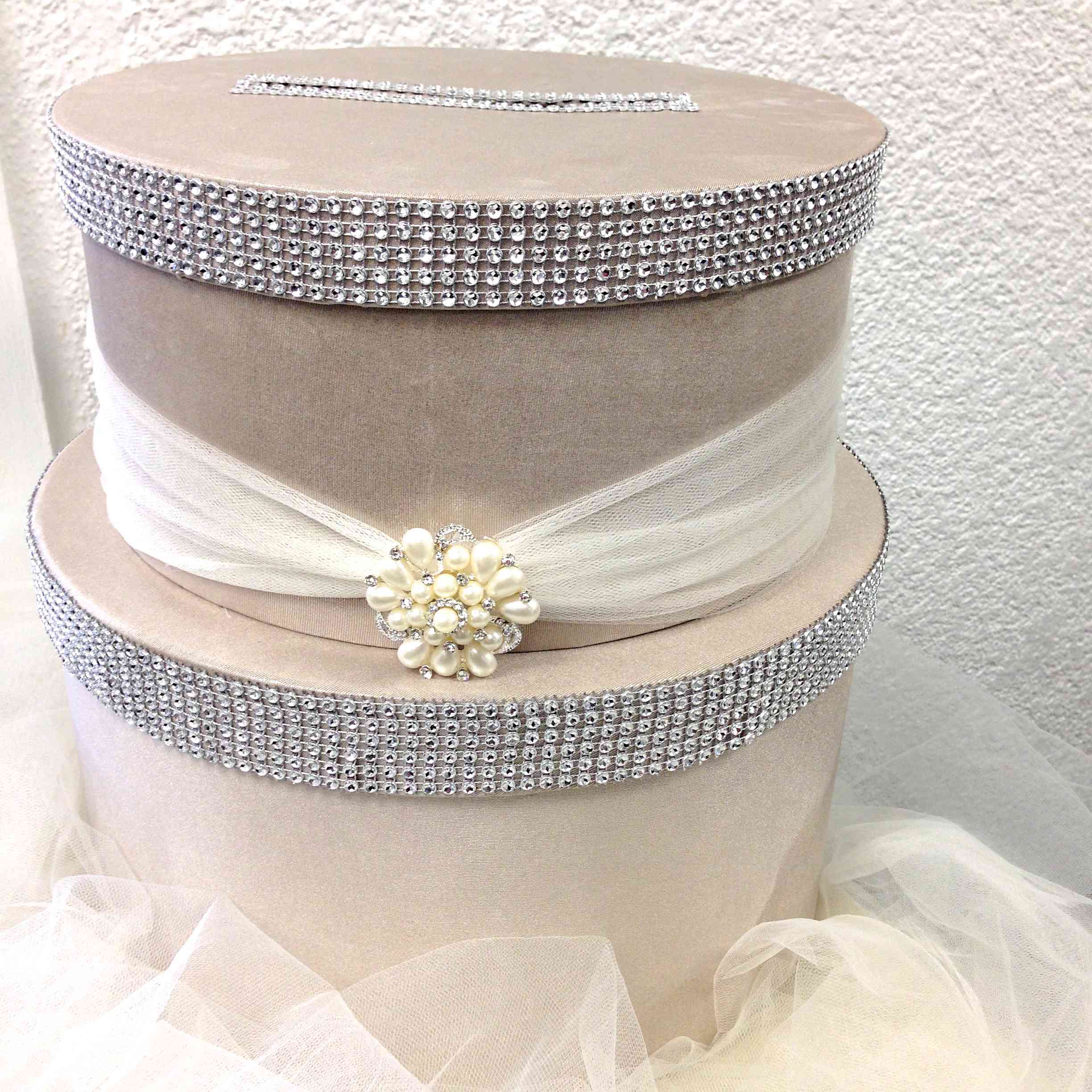 Tiered white wedding card box with embellishments.