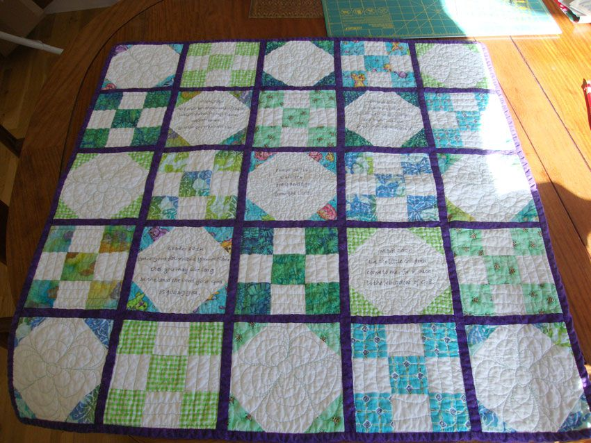 Baby quilt with squares of scripture lying on the table.