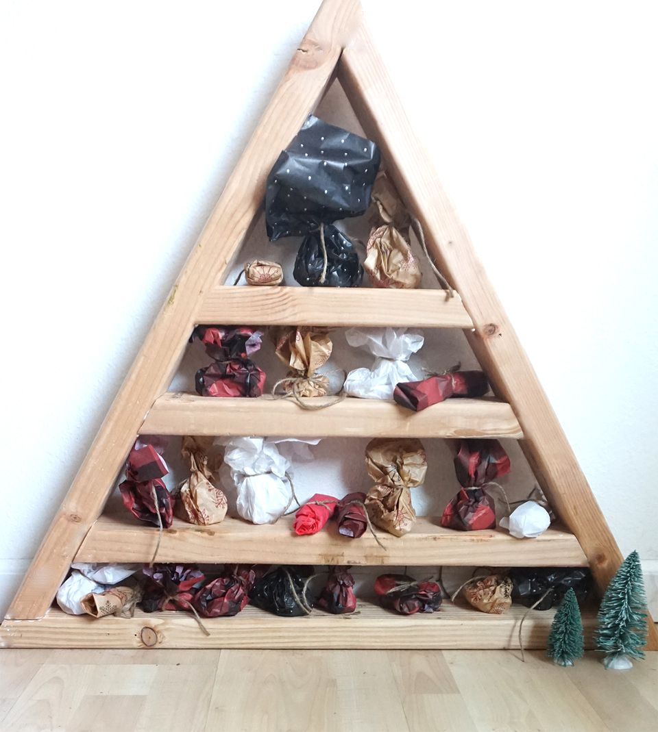 A wood triangle advent calendar with shelves filled with gifts.