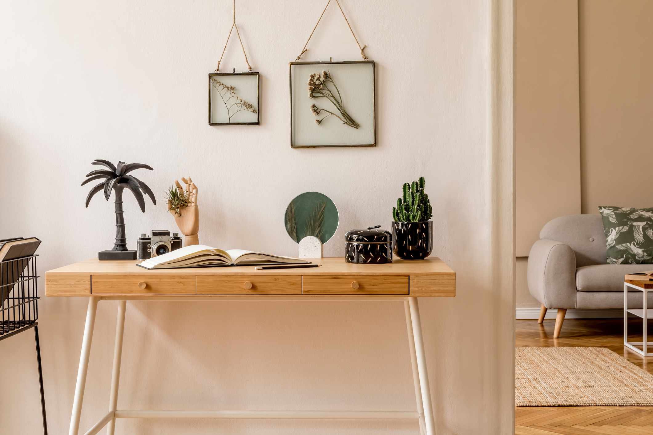 Interior design of scandinavian open space with mock up photo frames, wooden desk, gray sofa, cacti, books office and personal accessories. Stylish neutral home staging. Beige walls. Template.