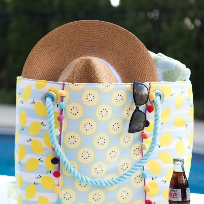 A yellow and blue beach bag by a pool