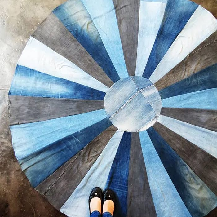 A woman standing on a rug made out of denim