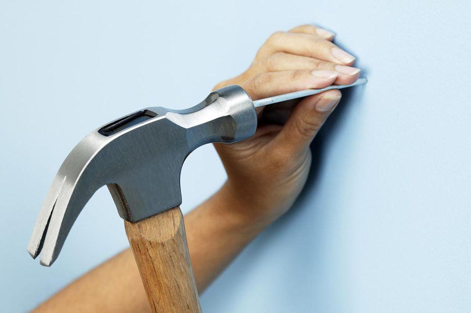 Woman hammering nail into wall