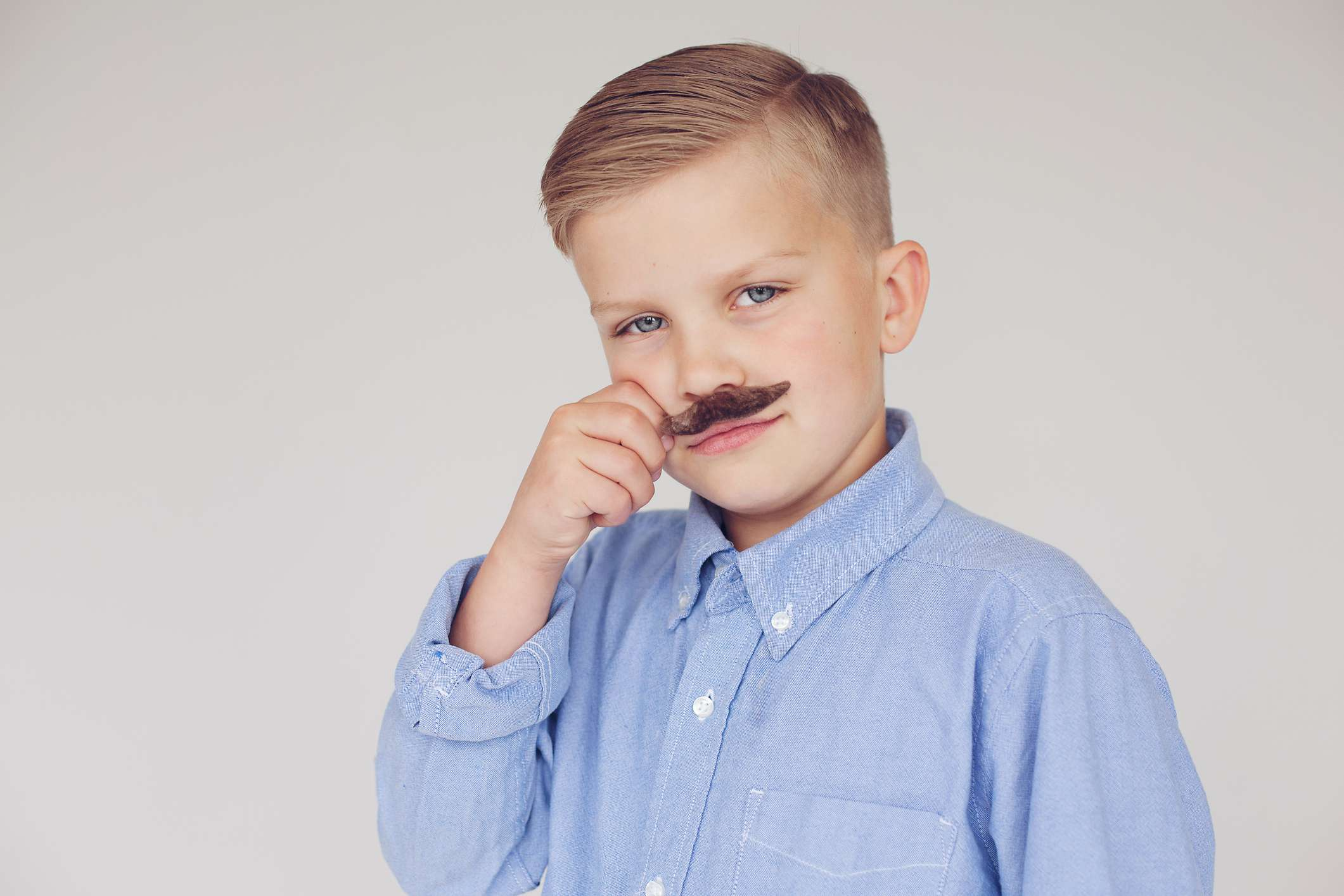 Young boy with fake mustache