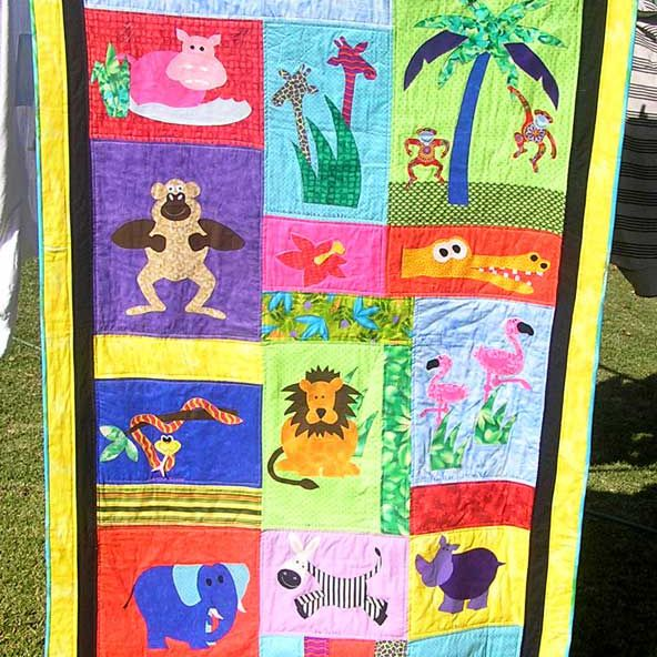 Baby quilt with jungle animals hanging on a clothesline with clothespins.