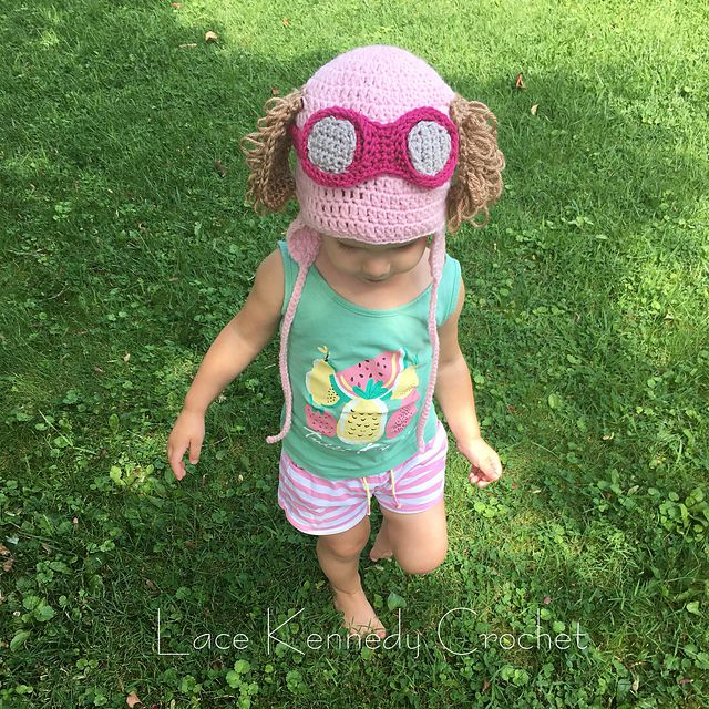 Toddler wearing summer clothing and a pink crochet hat with aviator sunglasses and puppy ears.
