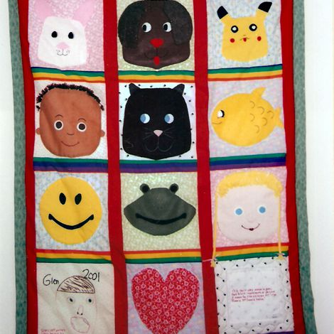Baby quilt with squares of children's and animal's faces.