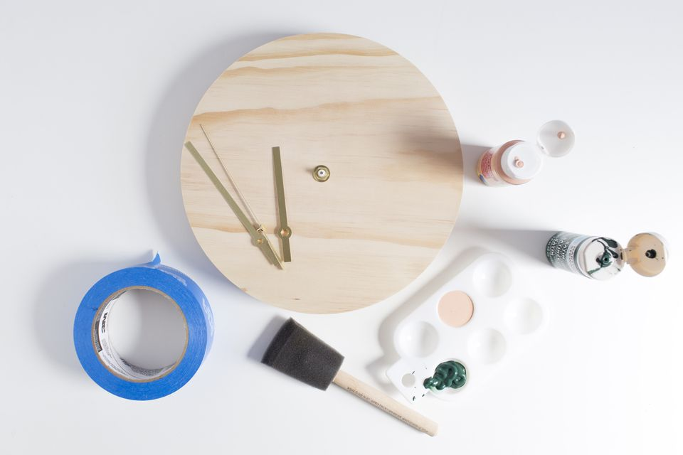 Supplies for creating your own custom clock, including paint, a paint sponge, a wooden clock kit, and masking tape