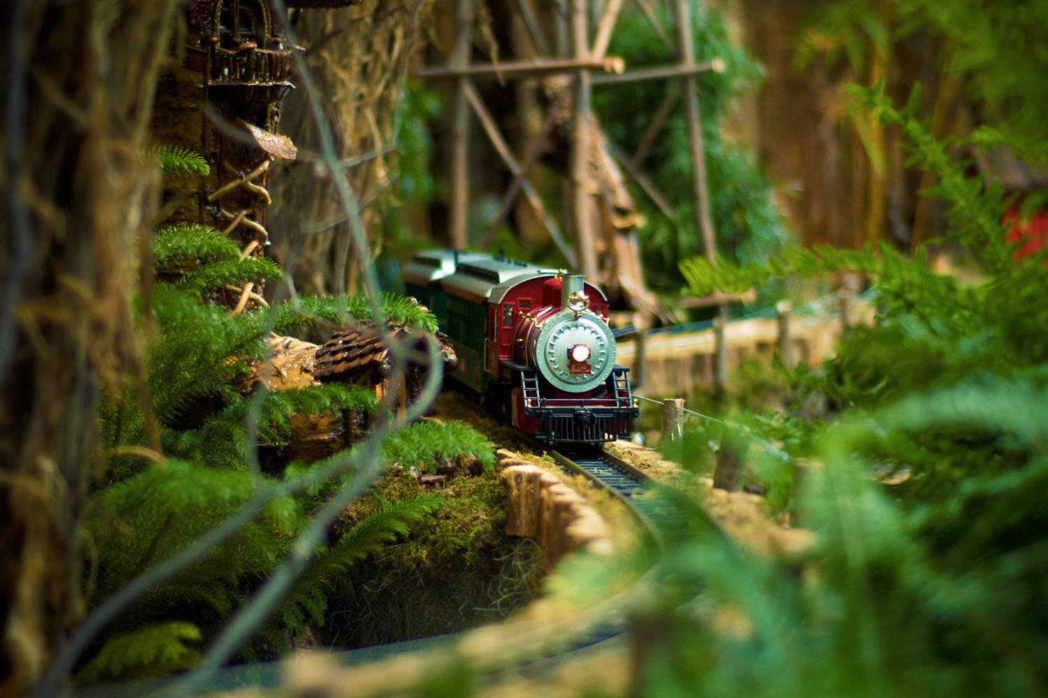Model train coming around a lush mountain