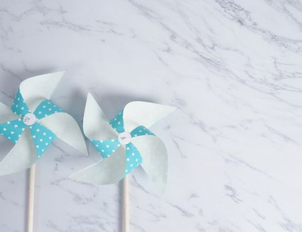 Wind wheel paper real toy on white color marble stone background which made from origami hand made on light blue colour japanese special material and wood stick for bay or kids playing.