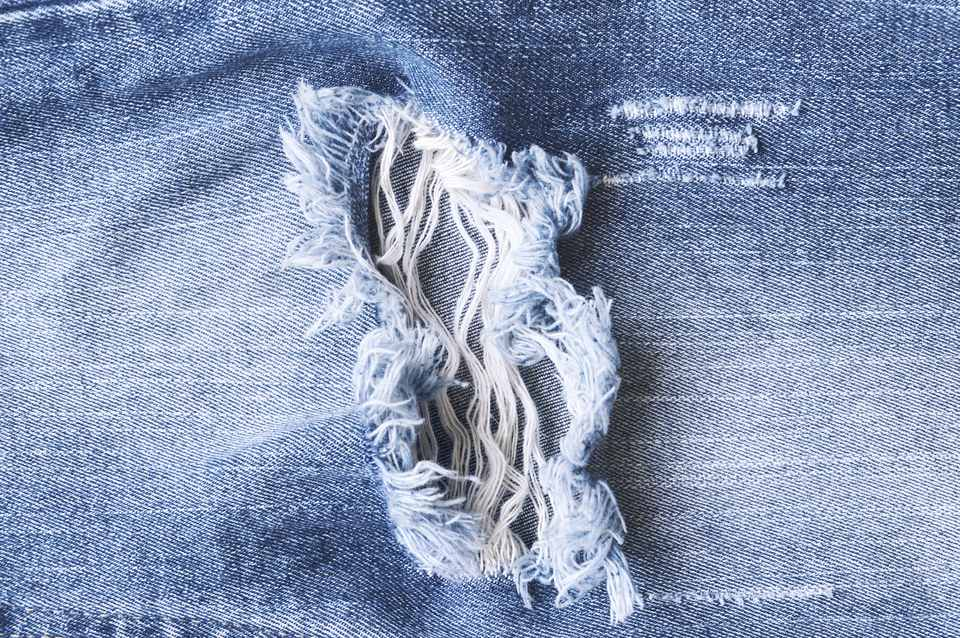 Hole and thread denim blue jeans, ripped torn jeans texture.