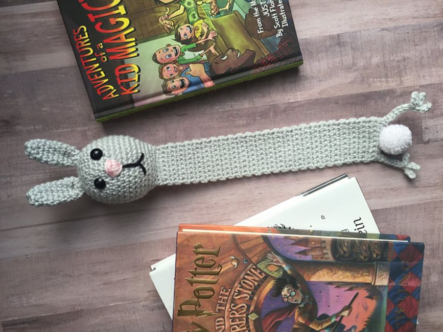 Bunny crochet bookmark on a desk with children's books