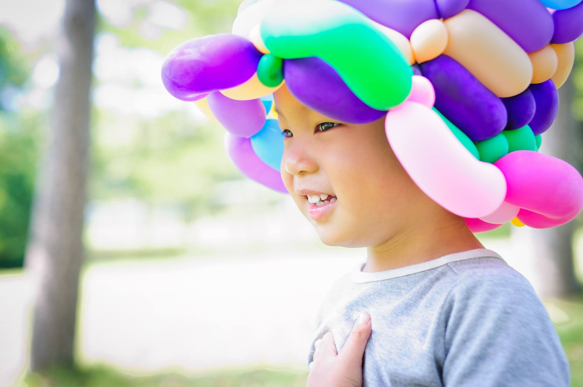 Boy wearing colored balloon hat