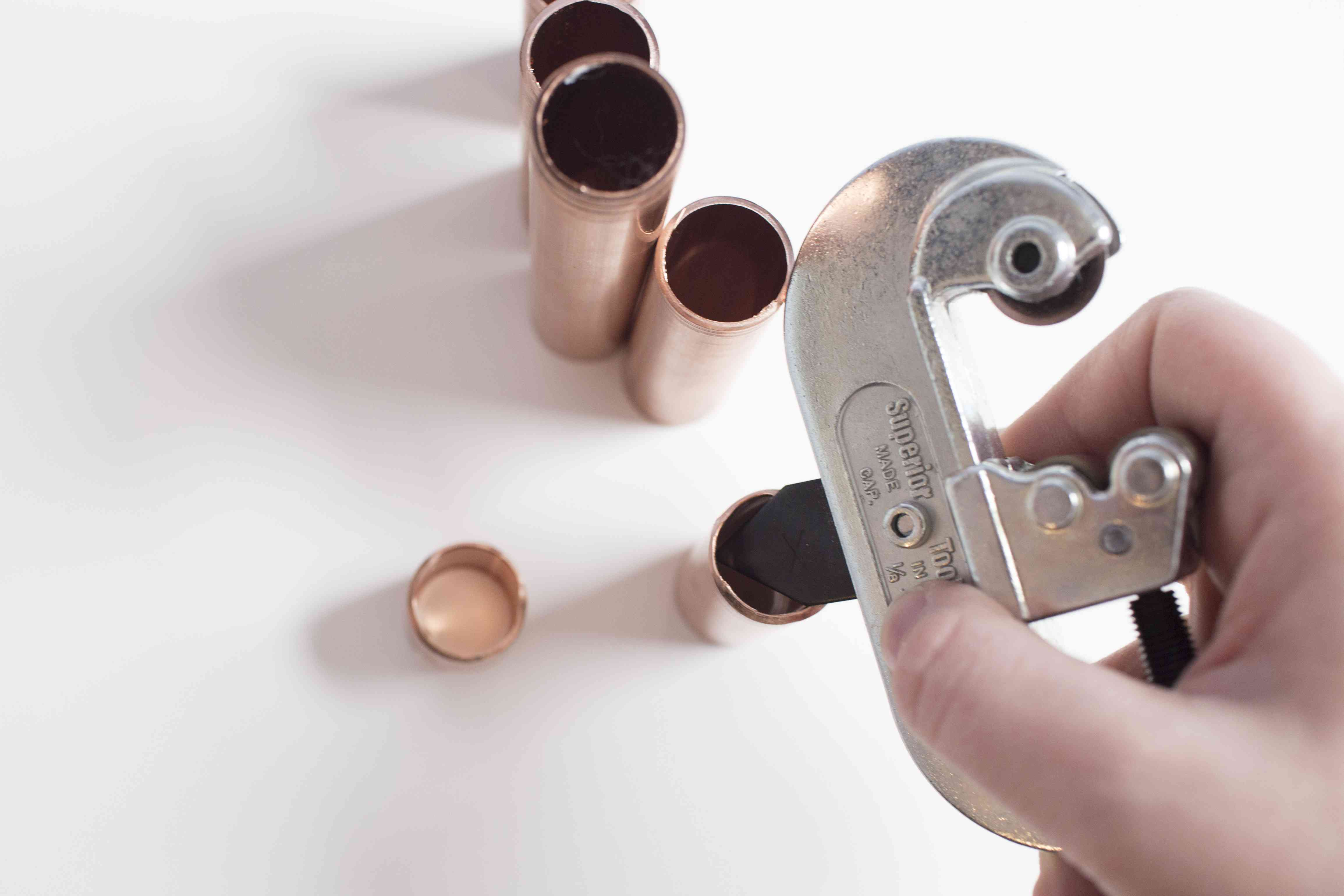 Using a pipe cutter smoothing out any uneven edges on the copper pipe pieces.