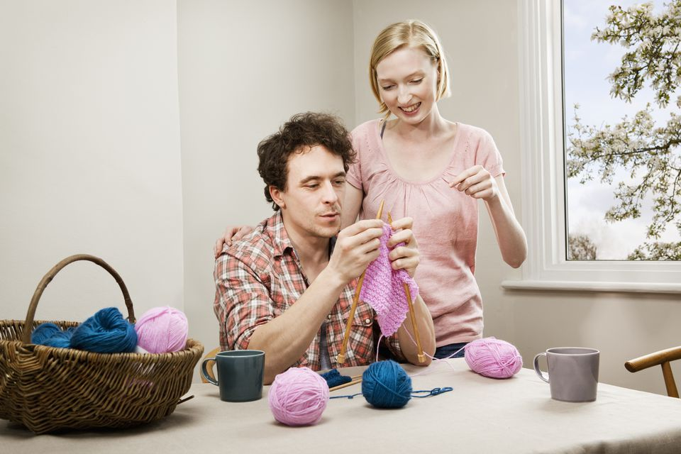 A woman teaches a man to knit
