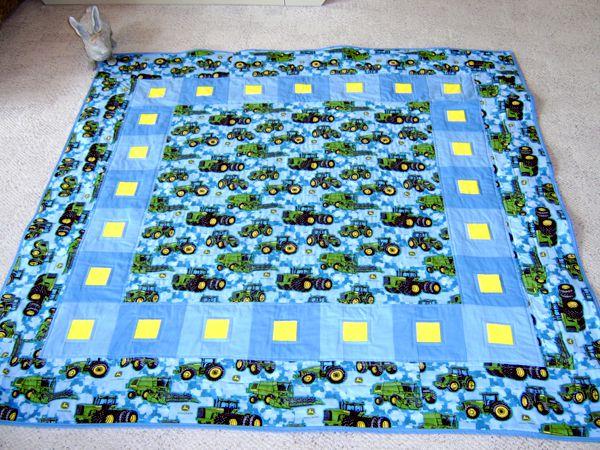 Blue baby quilt adorned with John Deere tractors.