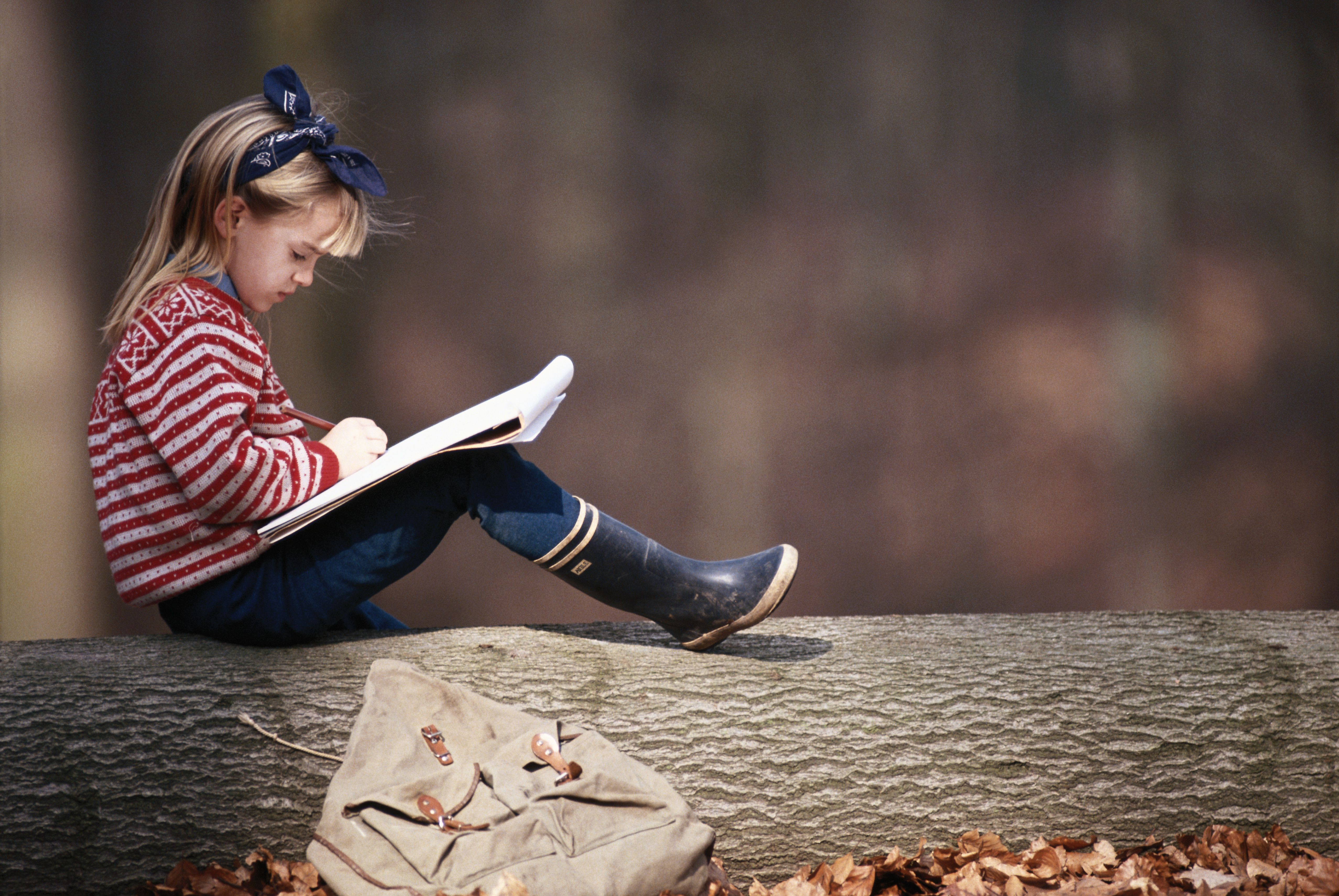 Girl (6-7) sitting on tree branch writing, side view
