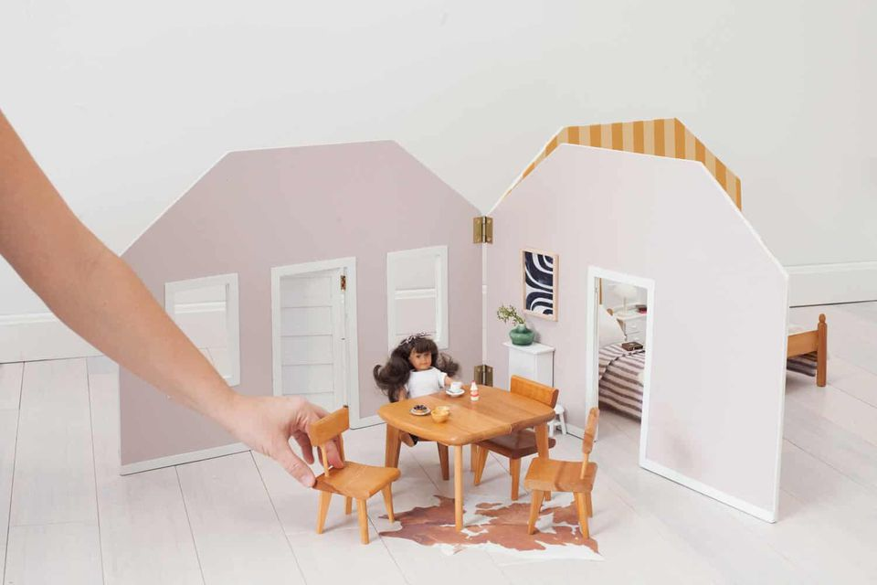 A woman setting up a dollhouse