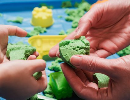 Parent and child playing with green kinetic sand