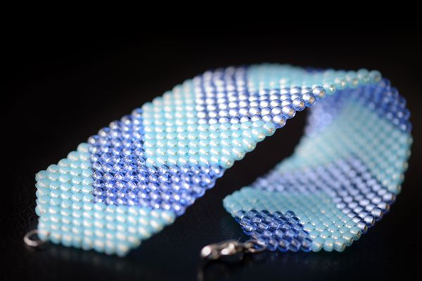 Blue peyote bracelet on a dark background close up