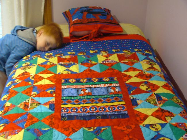 Boy resting his head on a Spiderman quilt with matching pillow.