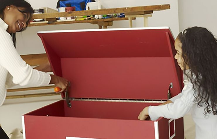 A mother and daughter putting hinges on a toy box